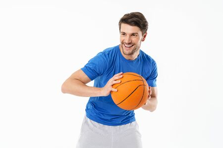 Attractive cheerful young fit sportsman wearing t-shirt isolated over white background, playing basketball Foto de archivo - 129242417