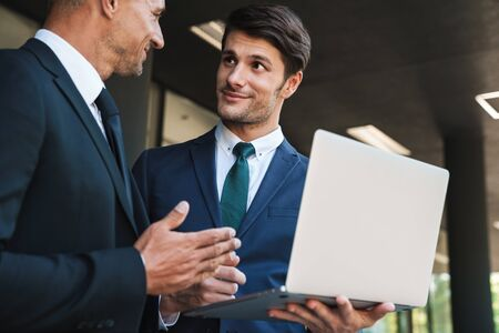 Portrait of successful businessmen partners dressed in formal suit standing outside office center and using laptop together during working meeting