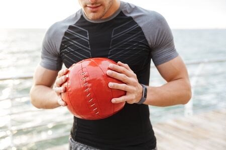 Cropped photo of a strong young sports man outdoors holding ball in hands. Stock Photo - 129823778