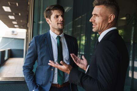Image of disagreed businessmen partners dressed in formal suit talking and discussing conflict while standing outside office center Stock Photo