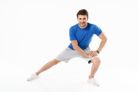 Photo of muscular athletic man in shorts and t-shirt doing sporty exercises while working out isolated over white background