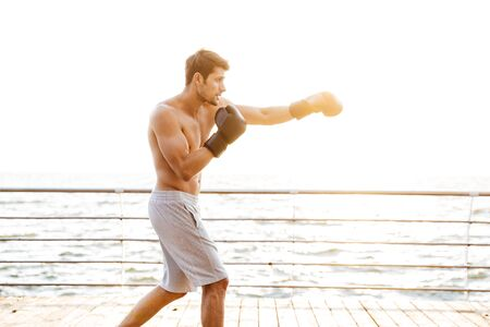 Photo of strong half-naked man working out in black boxing gloves on wooden pier at seaside in morning