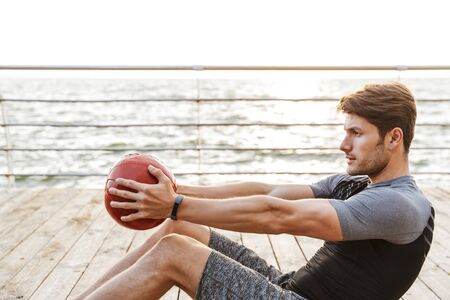 Foto de hombre caucásico en chándal haciendo ejercicio con pelota roja fitness mientras se ejercita en el muelle de madera junto al mar en la mañana
