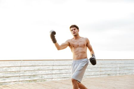 Photo of puzzled half-naked man working out in black boxing gloves on wooden pier at seaside in morning Фото со стока