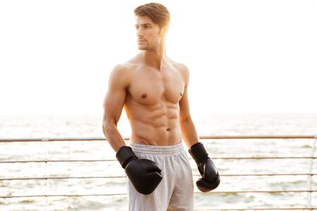 Photo of concentrated half-naked man looking aside while working out in black boxing gloves on wooden pier at seaside in morning