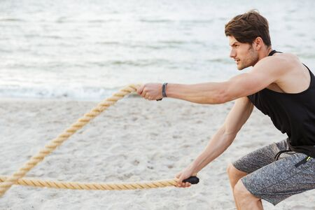 Photo of strong focused man in tracksuit working out with fitness rope on beach at seaside in morning