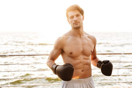 Photo of satisfied half-naked man looking at camera while working out in black boxing gloves on wooden pier at seaside in morning Фото со стока