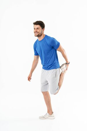 Full length of an attractive cheerful young fit sportsman wearing t-shirt standing isolated over white background, stretching leg