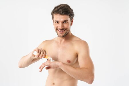 Photo closeup of young naked man smiling at camera and applying hand cream isolated over white background