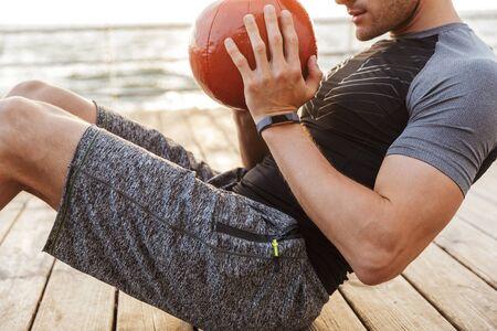 Foto recortada de hombre fuerte en chándal haciendo ejercicio con pelota roja mientras se ejercita en el muelle de madera junto al mar en la mañana
