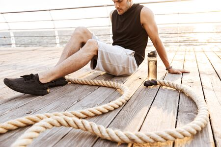 Photo of strong man 20s in tracksuit resting while working out with fitness rope on wooden pier at seaside in morning Фото со стока