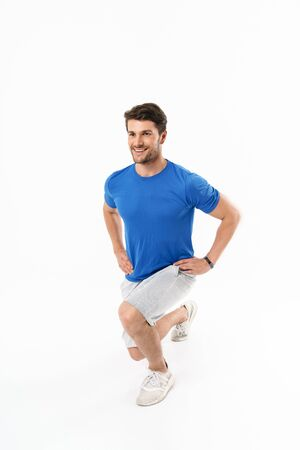 Photo of satisfied athletic man in shorts and t-shirt doing sporty exercises while working out isolated over white background