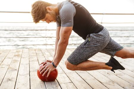 Photo of handsome man in tracksuit doing exercise with red fitness ball while working out on wooden pier at seaside in morning Фото со стока