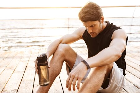 Photo of thinking man in tracksuit resting and drinking water while working out with fitness rope on wooden pier at seaside in morning
