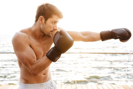 Photo of masculine half-naked man working out in black boxing gloves on wooden pier at seaside in morning