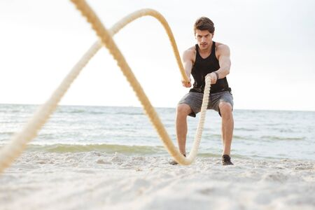 Photo of strong concentrated man in tracksuit working out with fitness rope on beach at seaside in morning