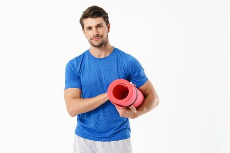 Photo of young man wearing casual t-shirt looking at camera while carrying fitness mat isolated over white background