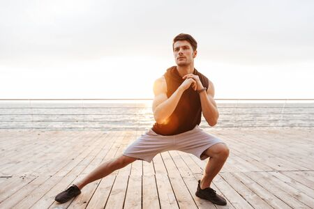 Photo of young man in tracksuit doing exercise while working out on wooden pier at seaside in morning