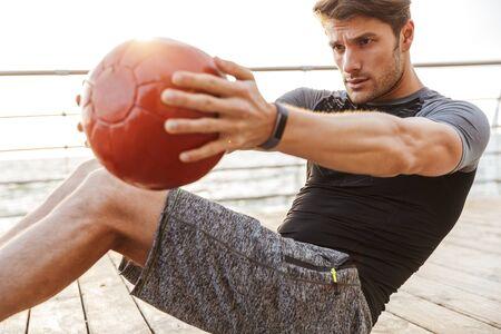 Foto de hombre enfocado en chándal haciendo ejercicio con pelota roja de fitness mientras se ejercita en el muelle de madera junto al mar en la mañana