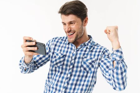 Photo of successful man in casual shirt playing video game on cellphone and clenching fist isolated over white background