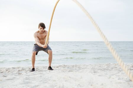 Photo of brutal half-naked man working out with fitness rope on beach at seaside in morning