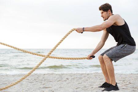 Foto de joven fuerte en chándal trabajando con cuerda de fitness en la playa junto al mar en la mañana Foto de archivo