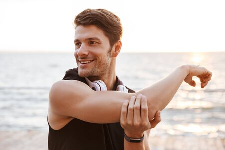 Photo smiling man in tracksuit with headphones doing exercise while working out at seaside in morning