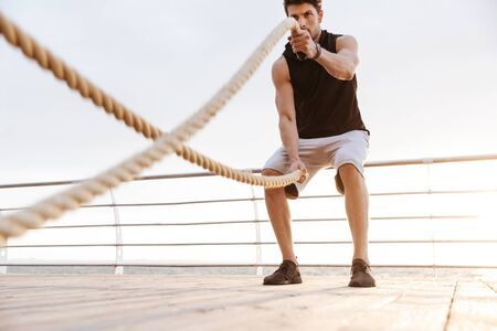 Photo of sporty man in tracksuit working out with fitness rope on wooden pier at seaside in morning Фото со стока