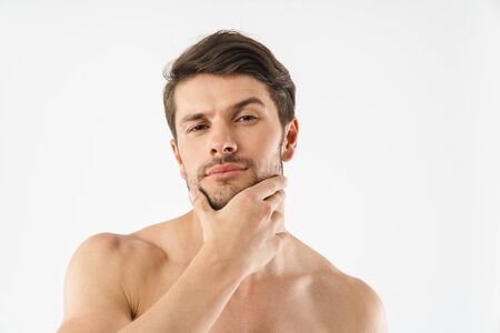 Close up of a handsome charming young shirtless man isolated over white background, touching his face Zdjęcie Seryjne