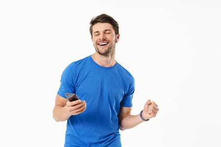 Photo closeup of happy man in casual t-shirt smiling and holding smartphone while wearing wireless earpods isolated over white background Stock Photo - 129259114