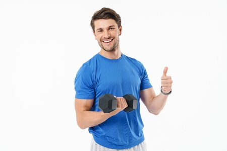 Attractive cheerful young fit sportsman wearing t-shirt standing isolated over white background, lifting heavy dumbbell, showing thumbs up Foto de archivo