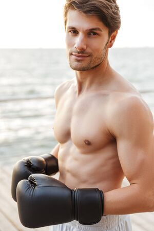 Photo of focused half-naked man looking at camera while working out in black boxing gloves on wooden pier at seaside in morning Фото со стока