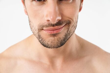 Close up half portrait of a handsome young shirtless man isolated over white background, grinning