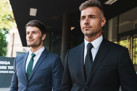 Portrait closeup of two entrepreneur businessmen partners dressed in formal suit walking together outside job center during working meeting