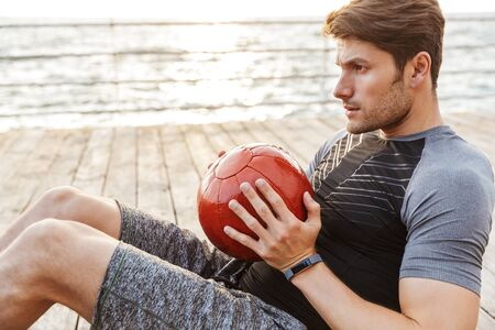 Photo of strong man in tracksuit doing exercise with red fitness ball while working out on wooden pier at seaside in morning