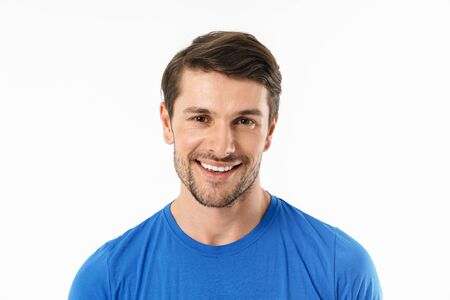 Photo closeup of brunette man in casual t-shirt smiling and looking at camera isolated over white background