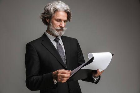 Bild eines kaukasischen erwachsenen Geschäftsmannes, der einen formellen schwarzen Anzug trägt und Papierdiagramme auf grauem Hintergrund hält