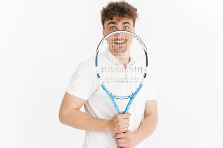 Photo closeup of excited man in t-shirt looking at camera and holding racquet while playing tennis isolated over white background