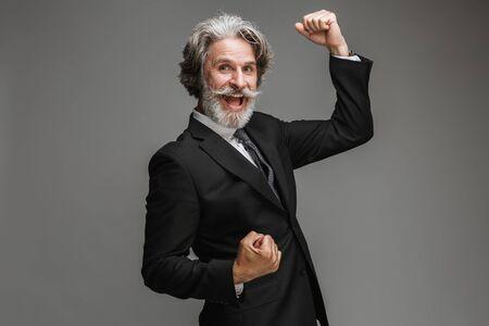 Image d'un homme d'affaires adulte réussi portant un costume noir formel se réjouissant et serrant les poings isolés sur fond gris