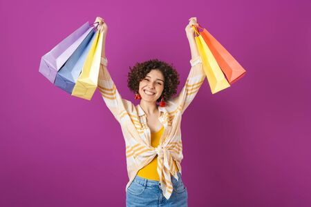 Portrait of an attractive cheerful young woman with curly brunette hair standing isolated over violet background, showing shopping bags