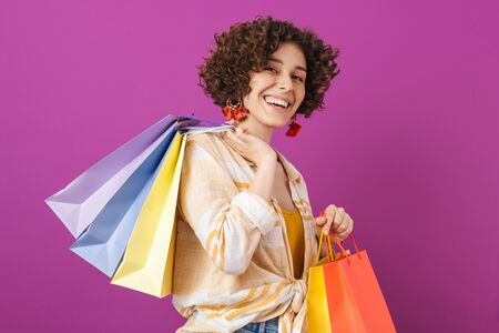 Portrait of an attractive cheerful young woman with curly brunette hair standing isolated over violet background, carrying shopping bags