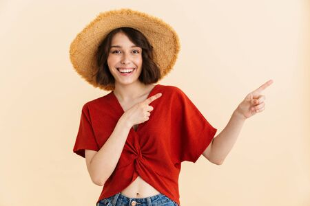 Portrait of happy brunette vacation woman wearing straw hat smiling at camera and pointing finger at copyspace isolated over beige background in studio