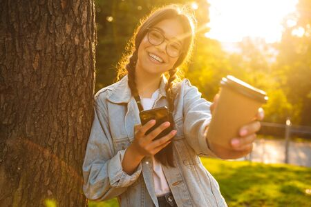 Image of a happy young teenage girl student walking outdoors in beautiful green park drinking coffee using mobile phone give you a cup.