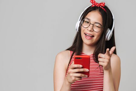 Cute cheerful teenage girl wearing casual outfit standing isolated over gray background, listening to music with headphones, using mobile phone, pointing at camera
