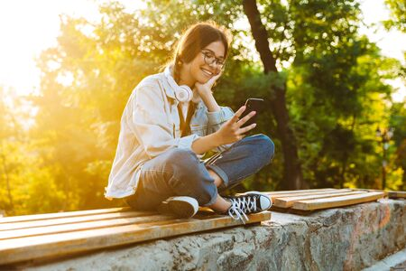Photo of a cheerful happy cute young student girl wearing eyeglasses sitting outdoors in nature park using mobile phone. Stok Fotoğraf