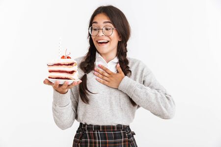 Photo closeup of happy teenage girl wearing eyeglasses smiling while holding big slice of birthday cake isolated over white background Stock Photo
