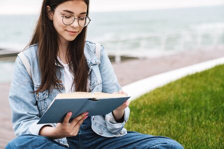 Image of thoughtful lovely teenage girl wearing eyeglasses reading book while sitting on green grass by seaside