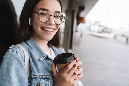 Image of satisfied smiling teenage girl wearing eyeglasses and earpods holding paper cup of takeaway coffee while walking outdoors Reklamní fotografie
