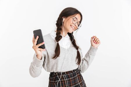 Attractive cheerful schoolgirl wearing unifrom standing isolated over white background, listening to music with earphones, holding mobile phone, dancing