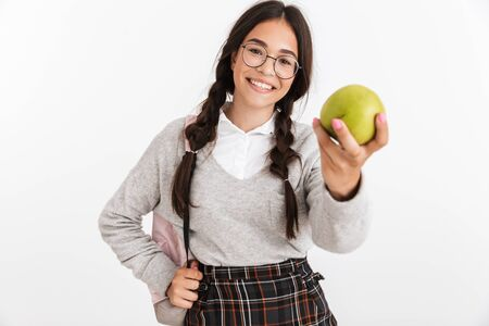 Photo closeup of caucasian teenage girl wearing eyeglasses and backpack eating green apple isolated over white background Stock Photo